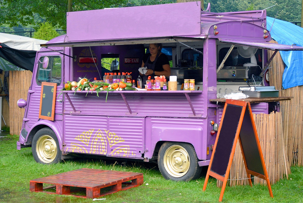 tata super ace food truck business is running on the parking side of the road.