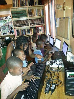 Sister Niya helping the children learn computer skills