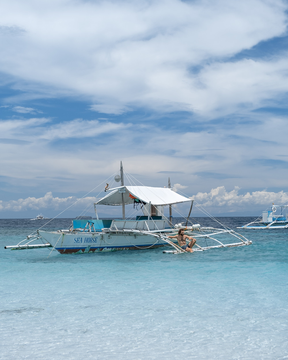 Sitting on a boat on Moalboal's white sand beach in Cebu island