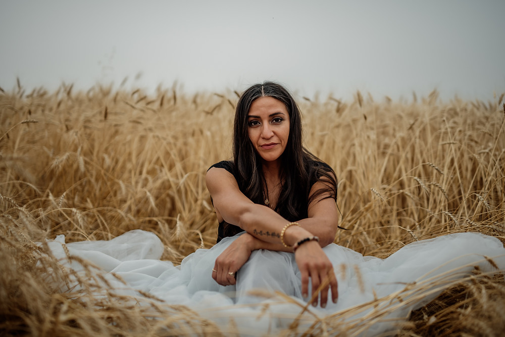 A Beautiful woman sitting in a wheat field.