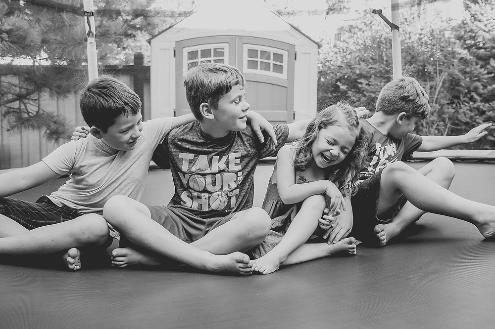 Four children, three boys one girl all under 10. Cousins all laughing and having fun sitting a trampoline. Black and whit image.