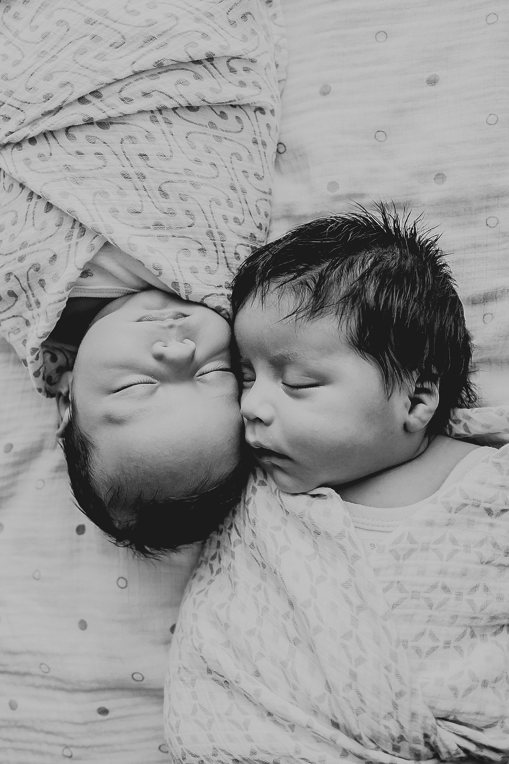 Twin newborn boys, cheeks together, heads in opposite directions, peacefully asleep.
