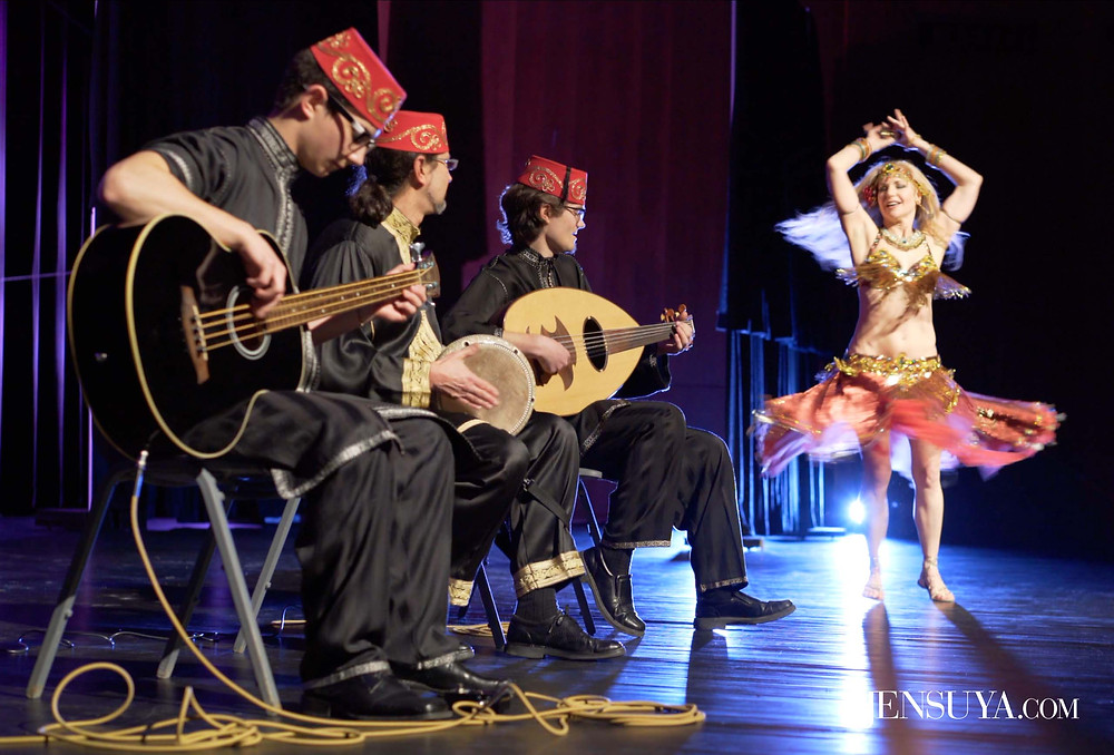 Belly dancer and live Middle Eastern band performing on stage.