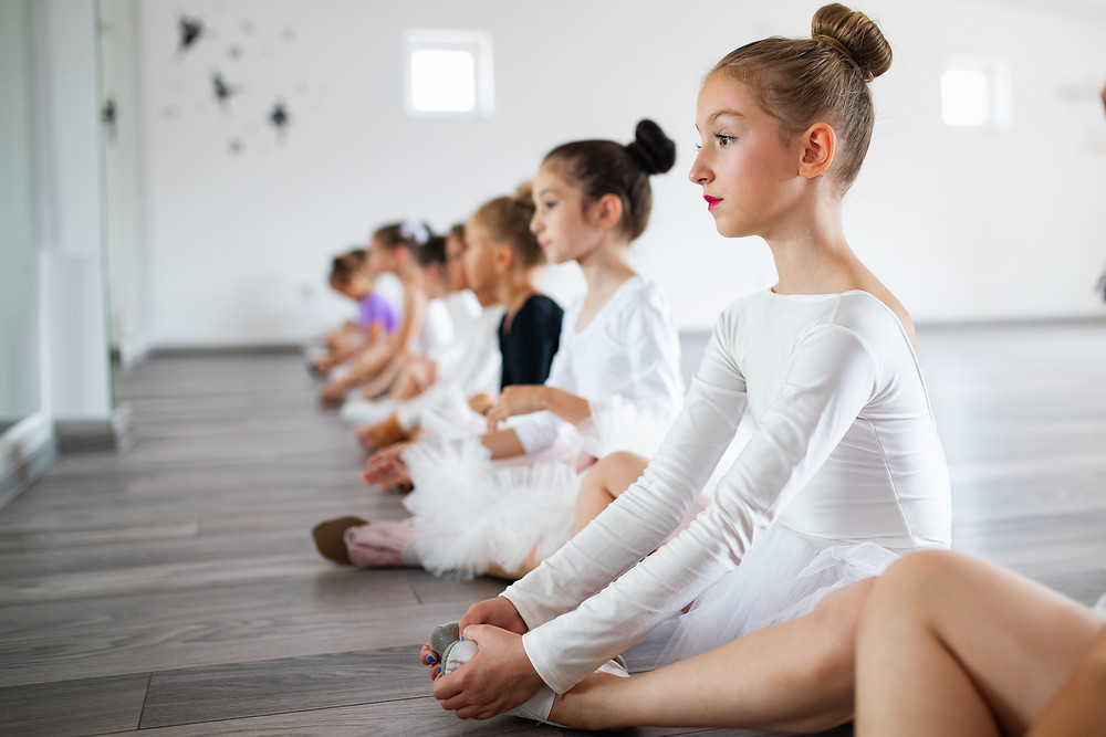 Line up of little girl ballet dancers stretching on the floor.