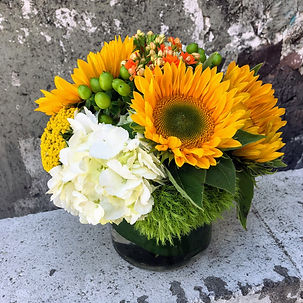 Pave design with bright sunflowers and pops of greens and oranges in a low cylinder container
