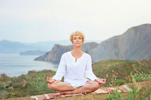 Senior woman doing yoga exercises with m