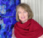 Photograph of artist Sonia Farrell smiling with artwork behind. The artwork behind is blue swirls with silver anchors