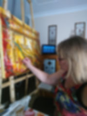 Photo of Sonia doing artwork 'Reflections of the King' at an easle in her studio