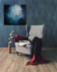 Reading Chair With artwork on wall next to it. Sonia Farrell's artwork is abstract style of light in deep ocean