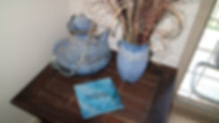 Image is a dark bali-style coffee table with two big light blue decorative pottery pots (one has flower and one is shaped like a tea pot) On the table is a copy of the Shine Art Collection artworks featuring various contemporary and abstract acrylic art digital images dshowcasing light and reflections to bring glory to God.These artworks are displayed in a quality hard cover book with thick pages and satin finish.