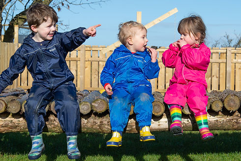 Three toddlers dressed in waterproofs and wellington boots engage in conversation whilst sitting on a man-made wooden bridge inside the nursery garden.