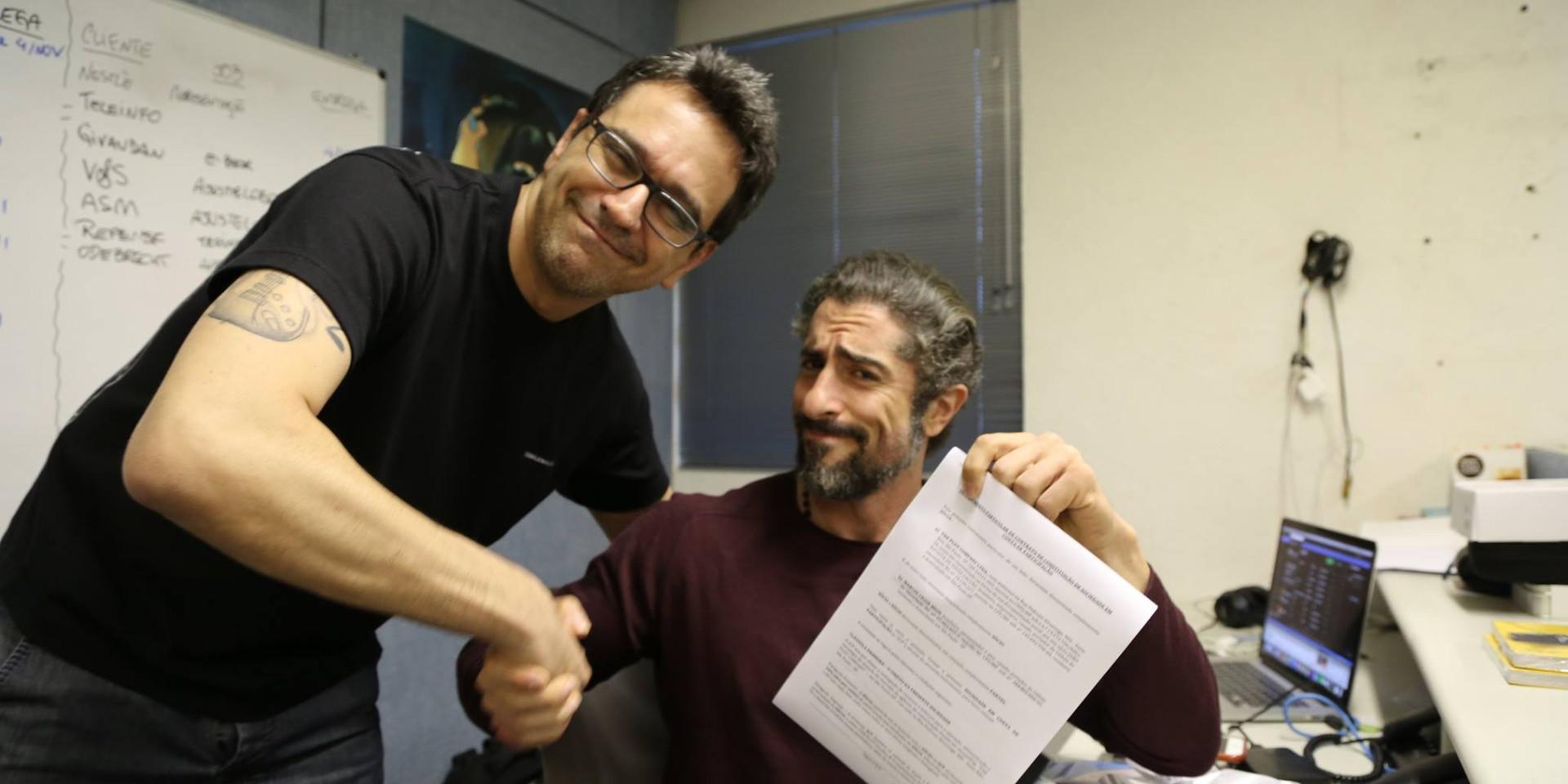 Joni e Marcos Mion assinando contrato