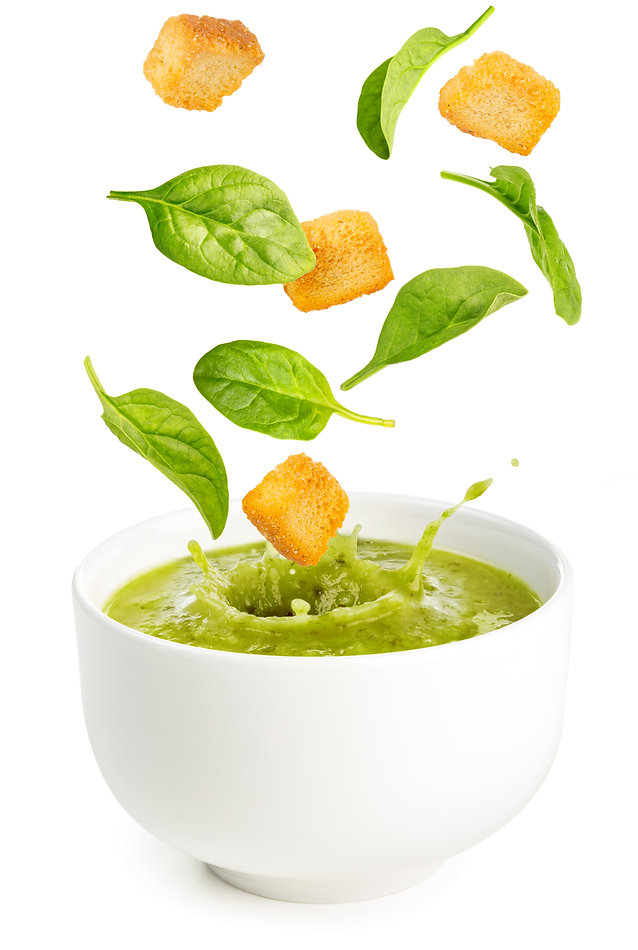 spinach leaves and croutons falling into