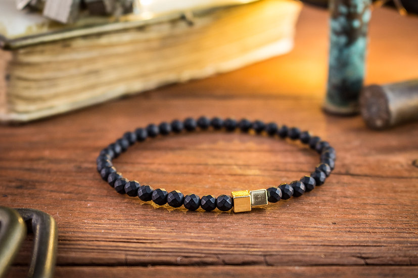 Matte black faceted onyx beaded stretchy bracelet with gold cubes