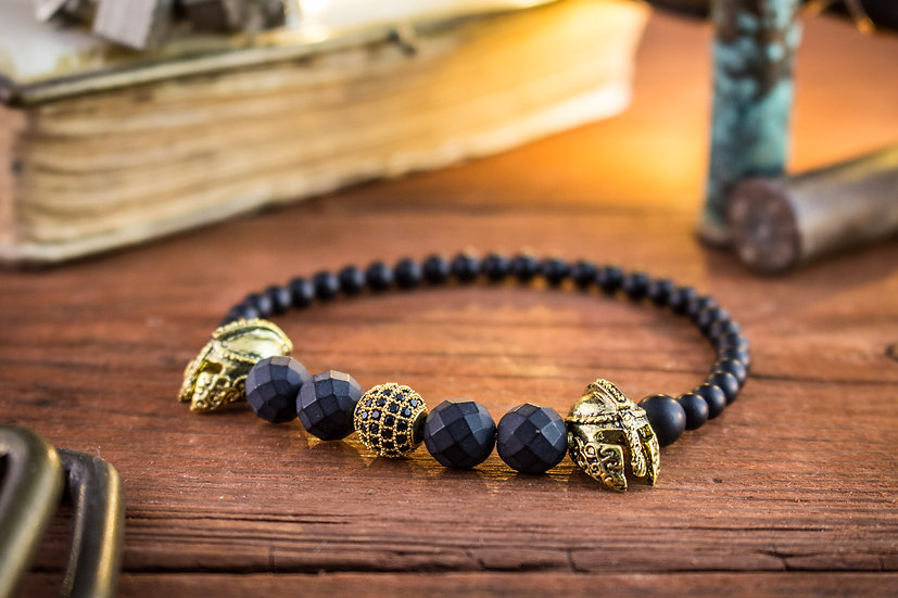 Matte black faceted onyx beaded stretchy bracelet with golden spartan warrior helmets