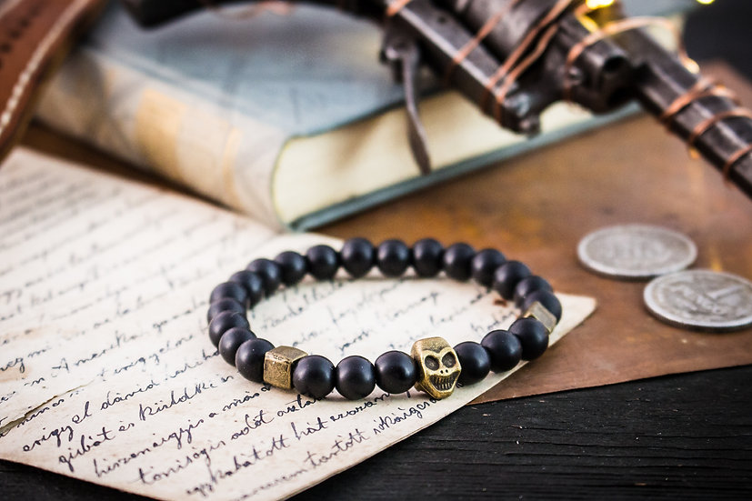 Matte black onyx beaded stretchy bracelet with bronze skull & accents
