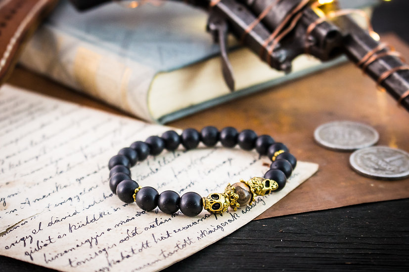 Matte black onyx beaded stretchy bracelet with gold skulls & accents
