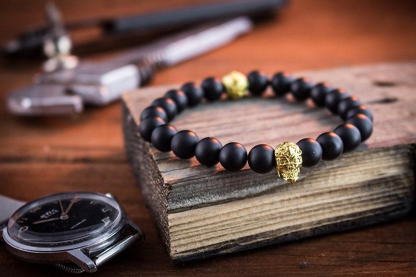Black onyx beaded stretchy bracelet with gold skull