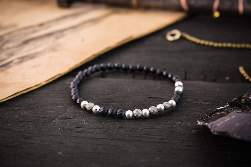 Matte black faceted onyx beaded stretchy bracelet with sterling silver accents