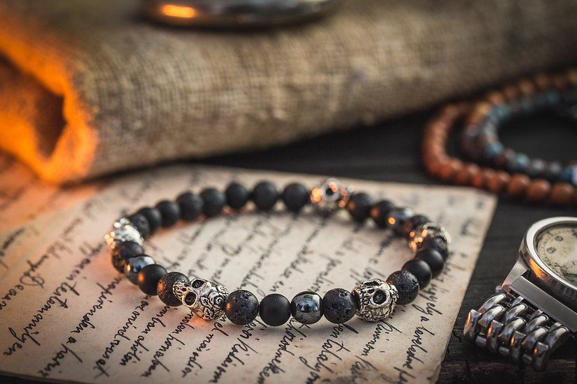 Black lava stone, onyx and hematite beaded bracelet with silver skulls