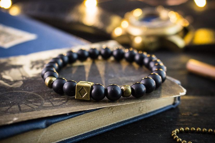 Matte black onyx beaded stretchy bracelet with bronze poker bead