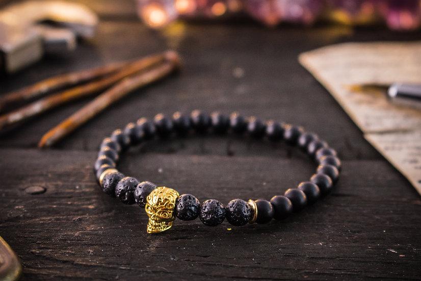 Matte black onyx & lava stone beaded stretchy bracelet with gold skull