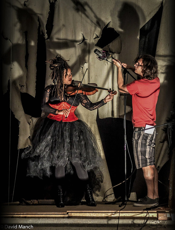 Nico Rivers setting up a microphone to record violinist, Rachel Jayson, while recording Walter Sickert and the Army of Broken toys in an abandoned theatre for the live video series, Live From Nowhere.