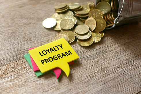 Gold coins and a stack of speech bubbles written with Loyalty Program on wooden background