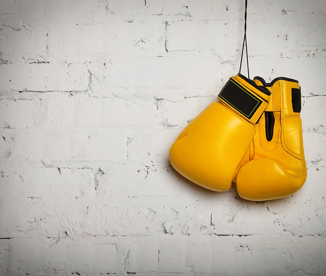 Pair of yellow boxing gloves hanging on