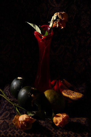 Still life with dead roses and dying vegetables