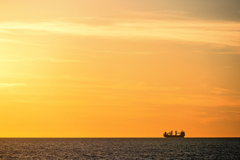 Cargo ship silouette in the sea at sunse