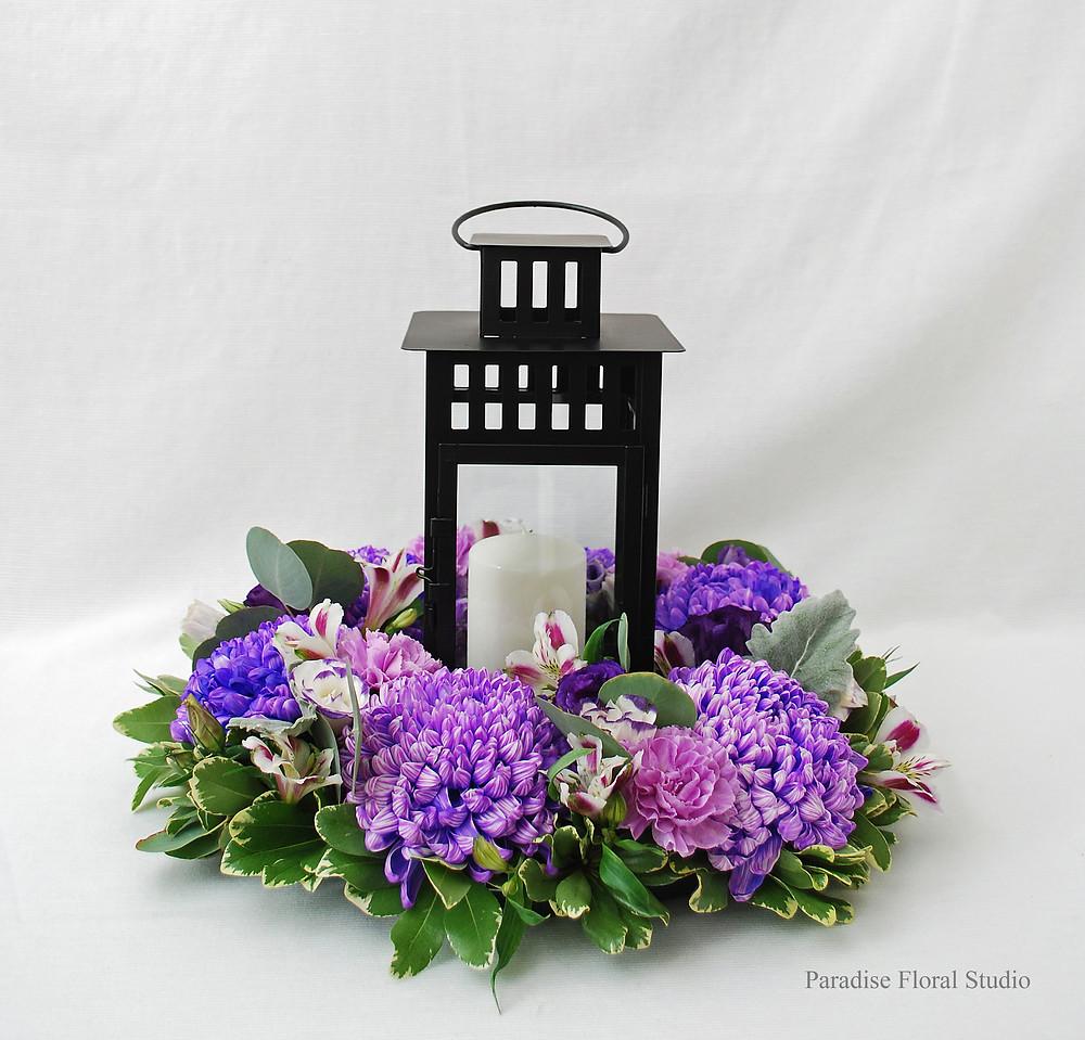 Table centrepiece, lantern, wreath, purple, white, lavender, wedding, commercial mum, alstroemeria, carnation, lisianthus, dusty miller, eucalyptus, paradise floral studio