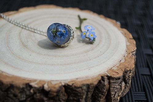 Handmade acorn pendant encapsulating pressed Forget me not flowers