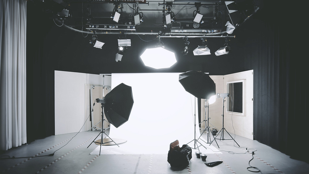 A photography studio is brightly lit and the light stands are visible in the photo