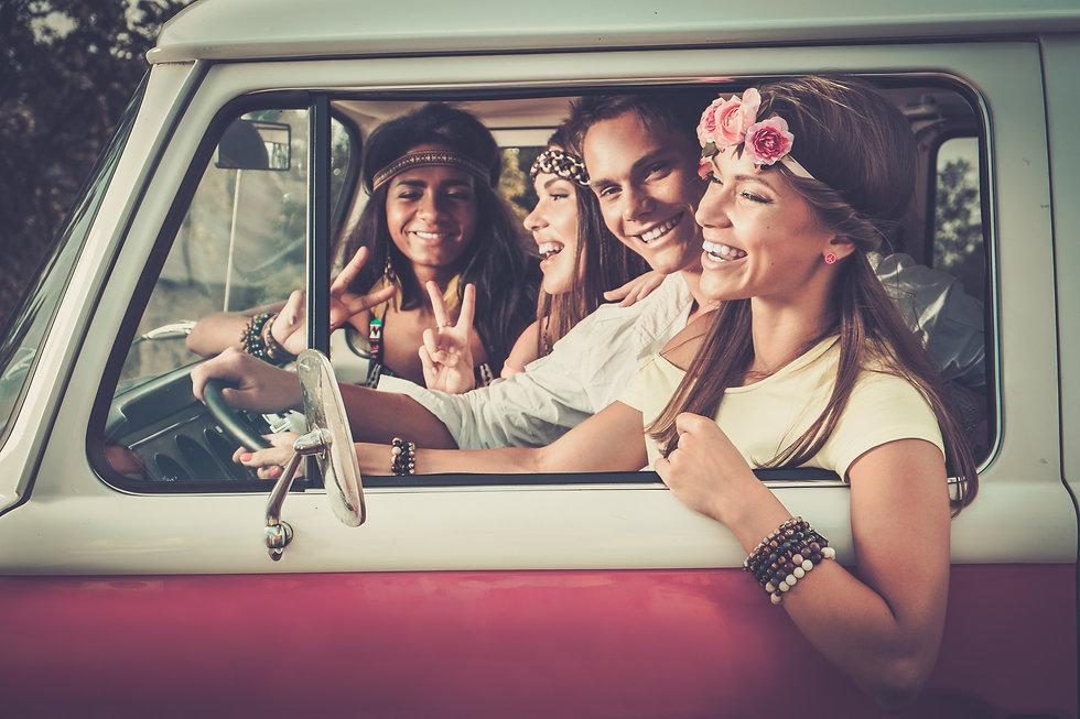 Multi-ethnic hippie friends in a minivan