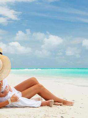 couple-sitting-on-beach-tropical-island-honeymoon-ocean-summer-shutterstock_151787042.jpg