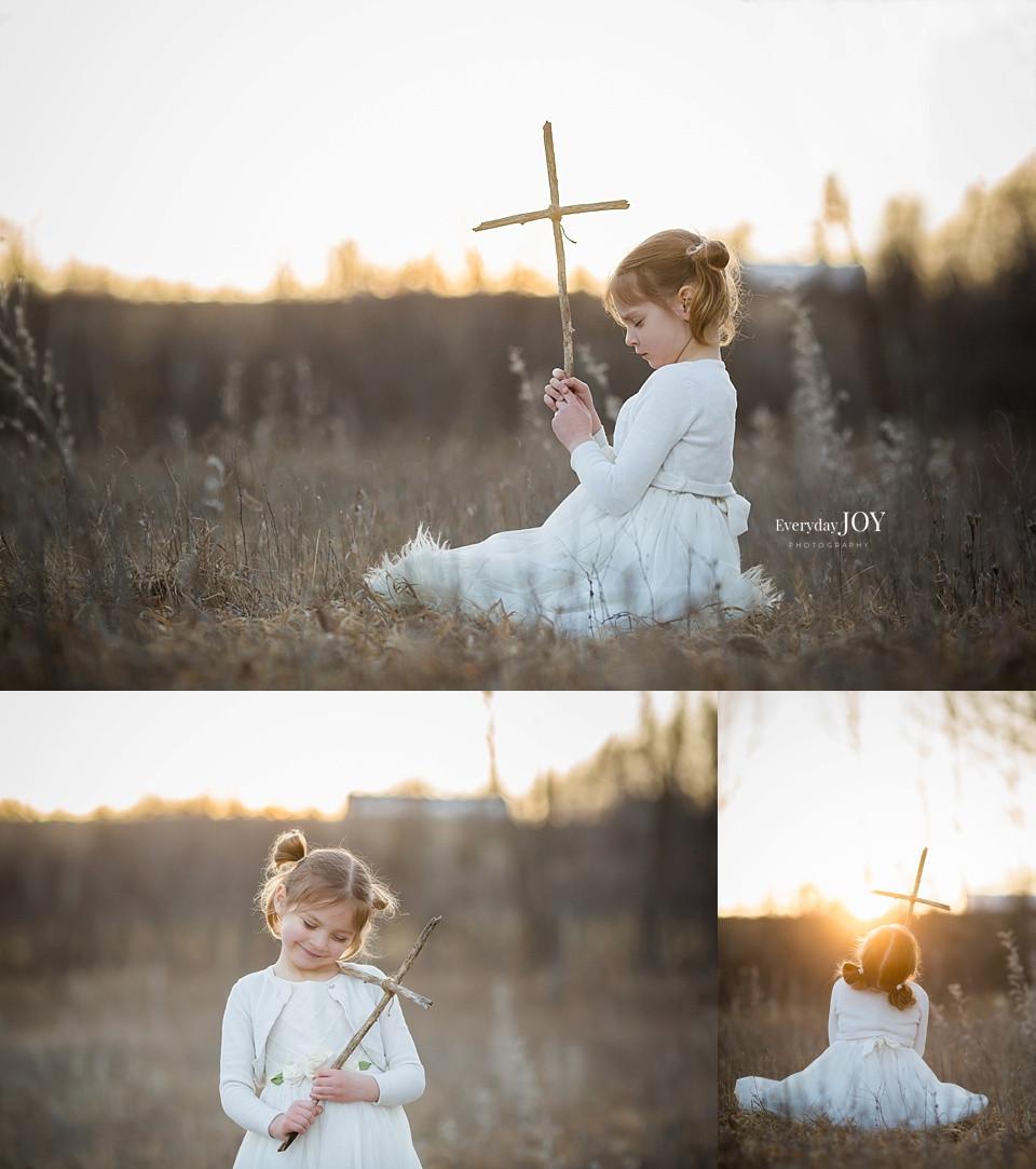 little girl holding wooden cross in field