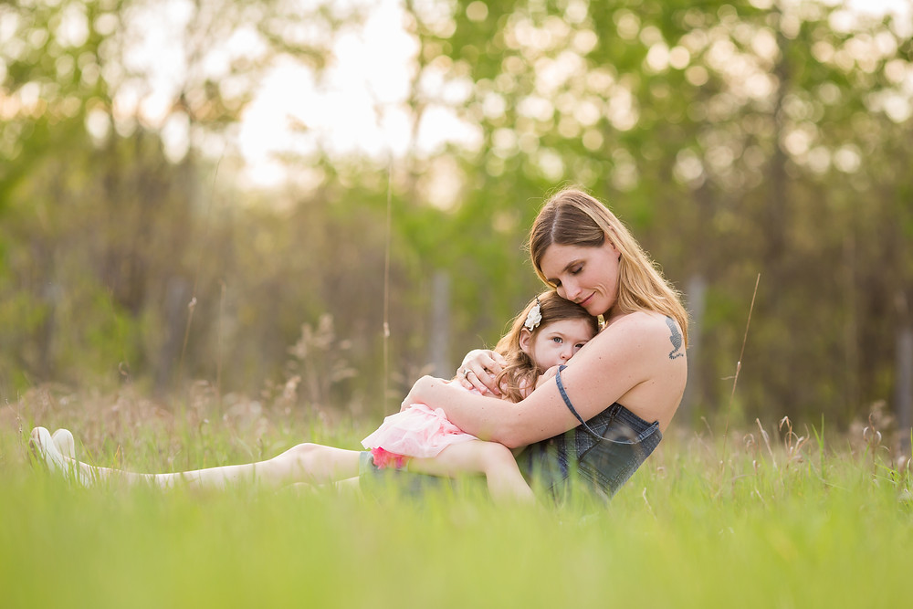 mom nursing older child in field
