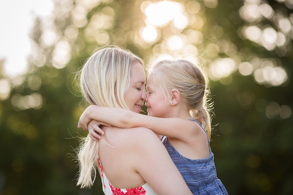 mom and daughter cuddling nose to nose in field