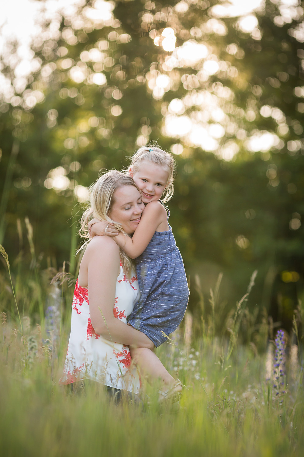 mom and daughter hugging in field
