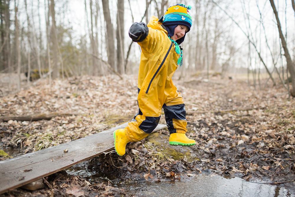 boy jumping off log into creek