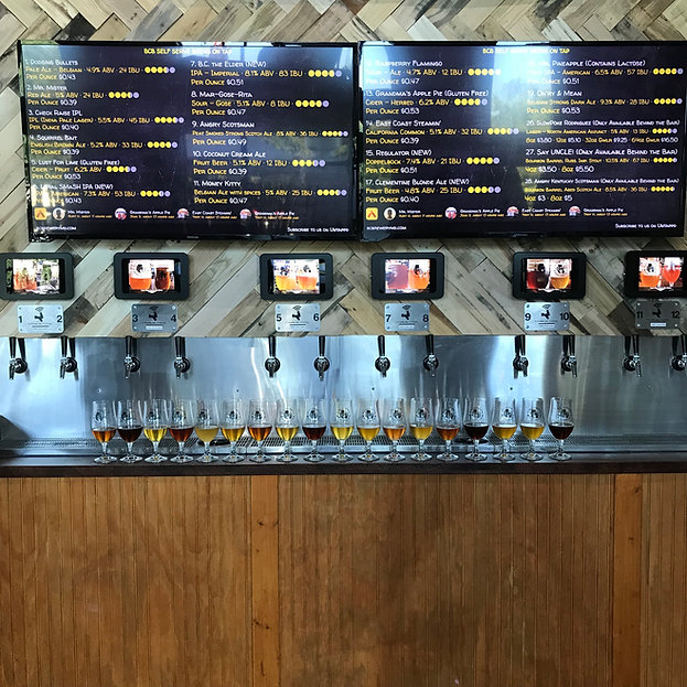 picture of the self serve wall and a line of beers in BCB glasses, partially filled