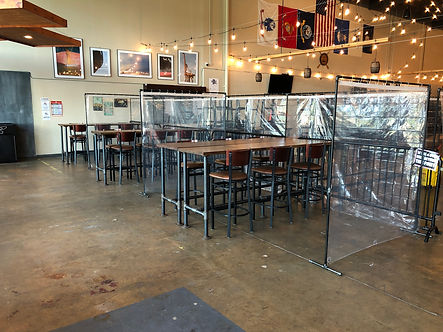 picture of the taproom with plastic barriers around tables for covid measures