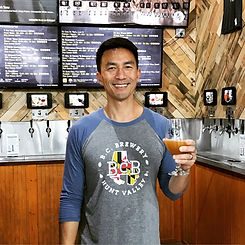 Rich Mak holding a beer, standing in front of the tap wall
