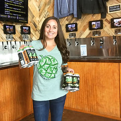 Sara Thomas standing in front of the self serve wall holding a 4 pack of cucumber melon gose and a 4 pack of dry humor cider