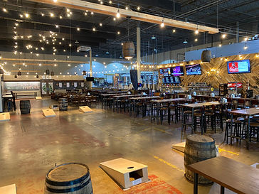 a picture of the taproom showing tables, cornhole boards, TVs, and the brewhaus in the background