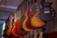 Des guitares électriques suspendues au mur d'un magasin de musique.