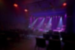 Une salle de spectacle avec une scène, des instruments de musique, des éclairages, de la fumée et des chaises.
