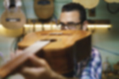 Un luthier observe la courbe du manche d'une guitare dans son atelier de réparation.