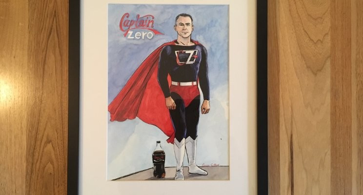 Photo of a framed coulour drawing of the author in a superhero costume titled 'Captain Zero'